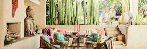Asian-inspired covered patio with colorful textiles and wicker furniture