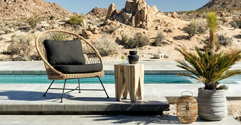 Poolside patio design in the desert with pretty decor and rattan chair