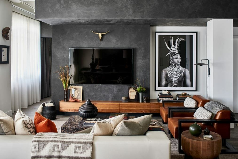 Striking living room design with charcoal walls, leather accent chairs and tribal photograph by one of the top Atlanta interior designers