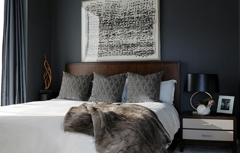 Transitional bedroom design with sheet music as wall art and plush bedding by one of the top Atlanta interior designers