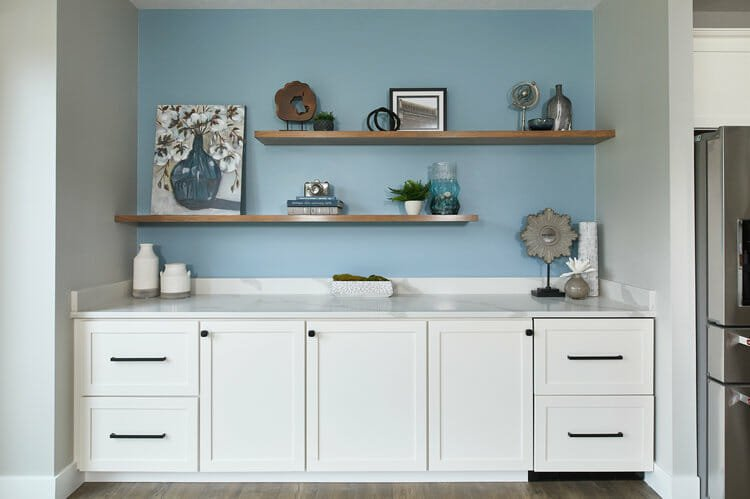 Beautiful organized shelves with a bright light blue wall, available as an interior design gift certificate by W Haus