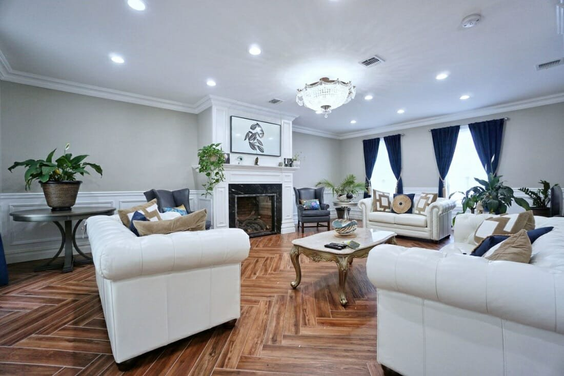 Glamorous traditional home style living room with blue velvet curtains, chandelier and Chesterfield sofas
