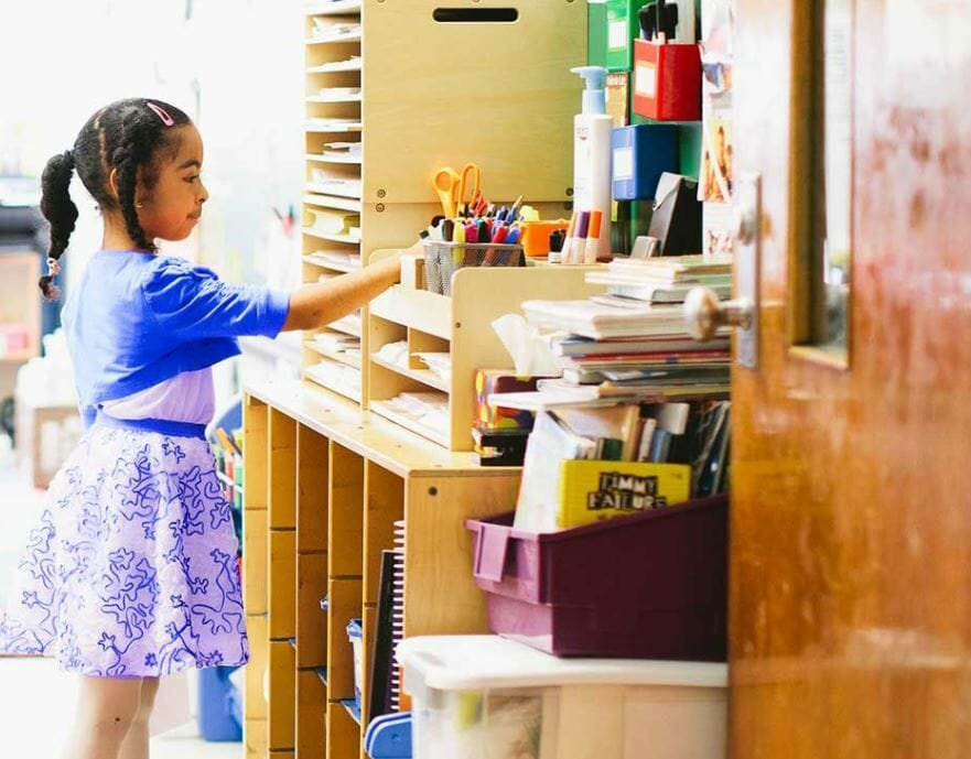 Young girl looking at stationary in a school that could benefit from Donors Choose's gift certificate ideas
