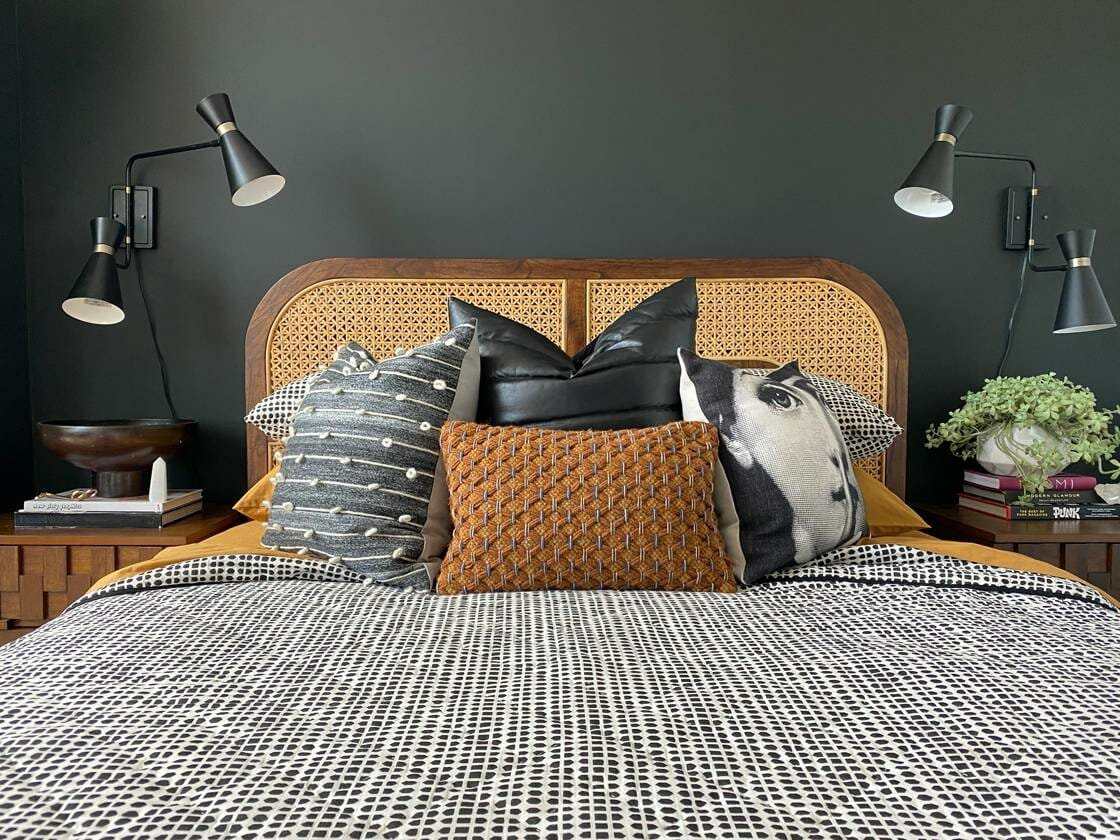 Grey and white bedding on a wicker bed as a CB2 Black Friday furniture sale