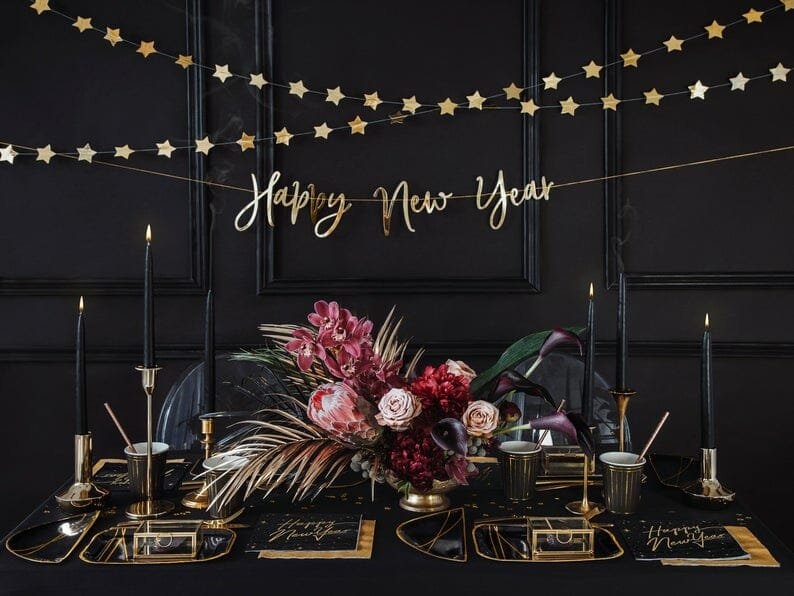 New year wall decoration next to a dramatic black new years dinner table