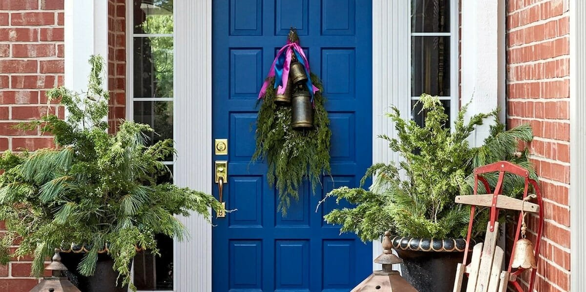 Evergreen fronds and bells winter door decoration