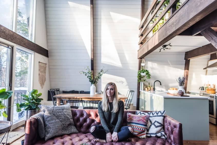 Woman sitting on a leather sofa in a loft apartment