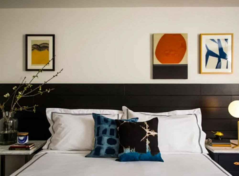 Bedroom with two-tone walls and colorful artwork