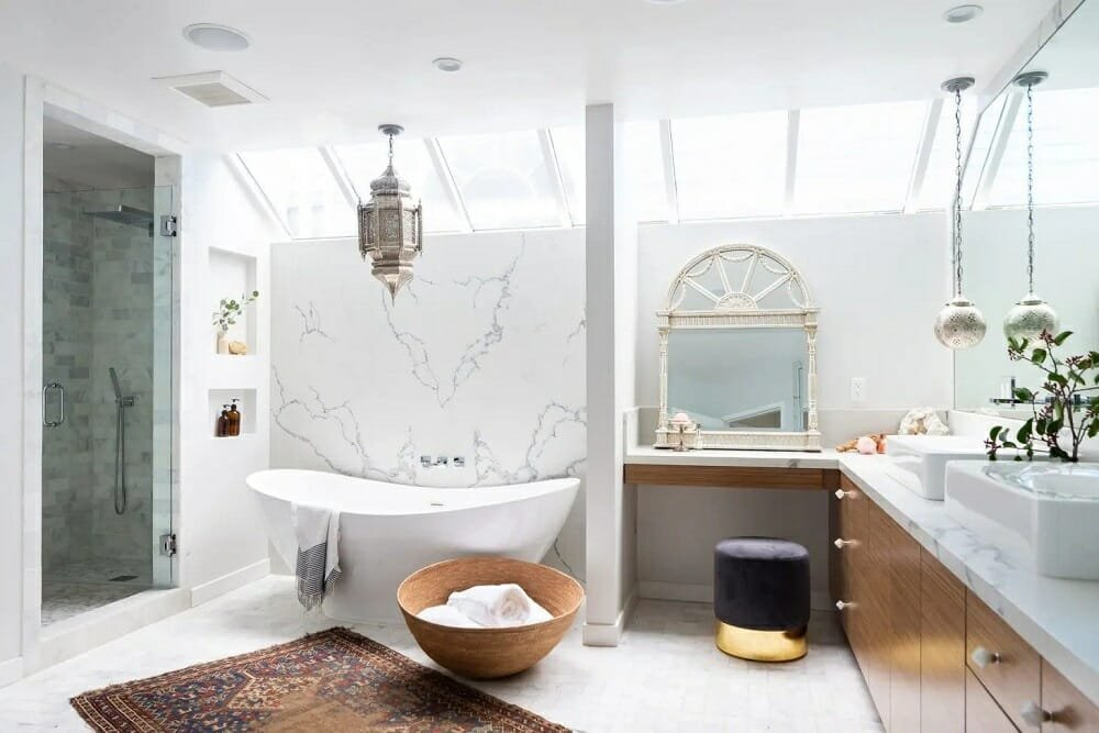 Freestanding bathtub with a chandelier, rug and ornate mirror in a large bathroom on trend for master bathroom trends