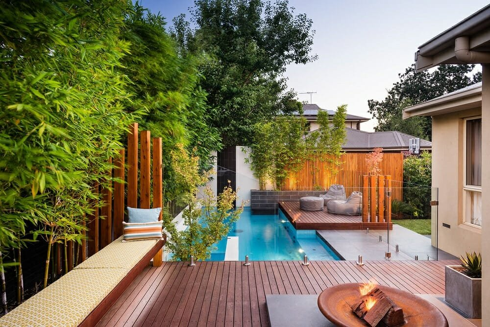 luxury pool with poolside furniture and screens - houzz